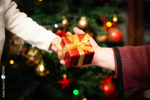 Photo クリスマスプレゼントを手渡す老人と孫の手
