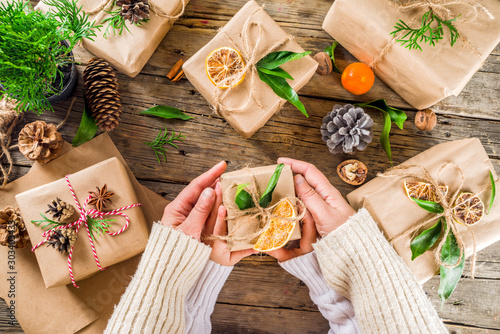 Female and kids hands decorate christmas gift box Fototapet