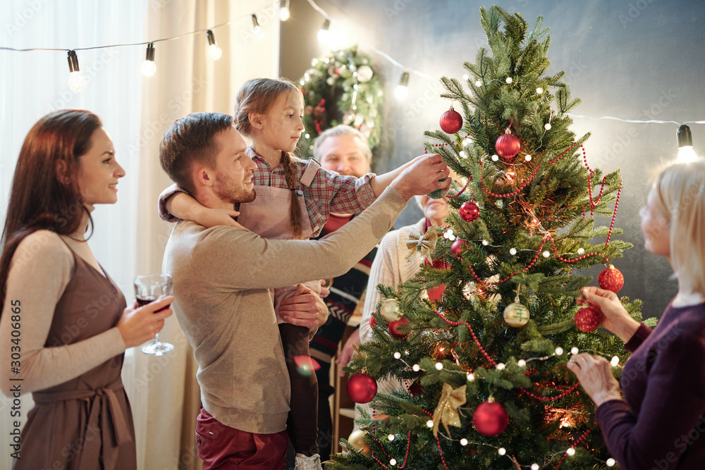 Fototapety, obrazy: Young man with his little daughter decorating Christmas tree at home