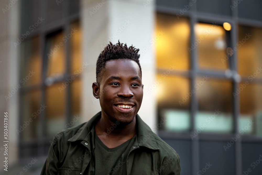 Fototapeta portrait of smiling african-american man in stylish jacket on city street in the evening.