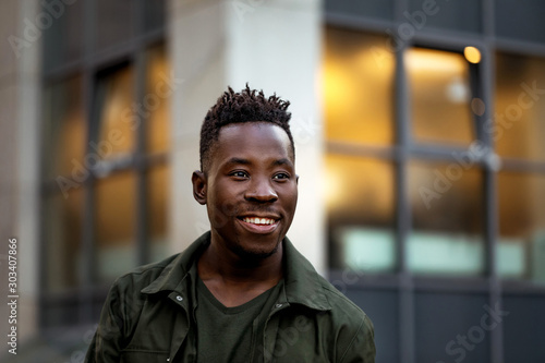 Obraz portrait of smiling african-american man in stylish jacket on city street in the evening. - fototapety do salonu