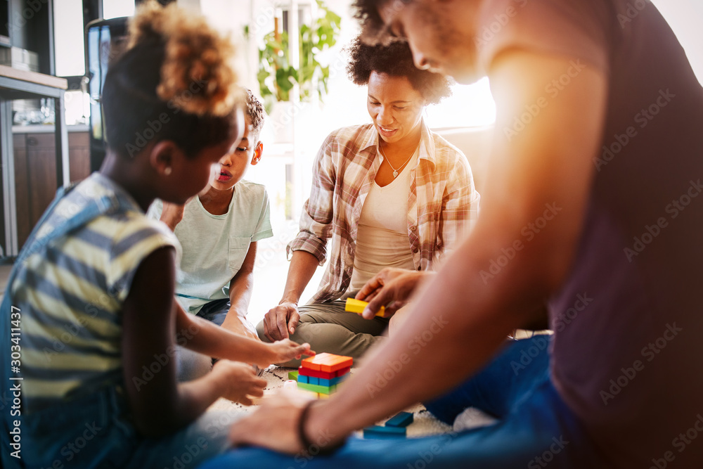 Fototapeta Happy black family playing game together at home