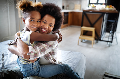 Happy mother playing, having fun, hugging with her daughter at home