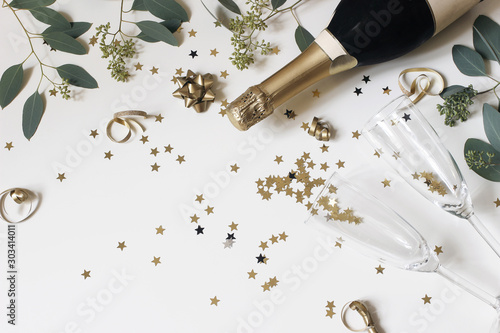Obraz Happy New Year composition. Champagne glasses nad wine bottle with golden confetti stars and eucalyptus branches isolated on white table background. Celebration, party concept. Flat lay, top view. - fototapety do salonu