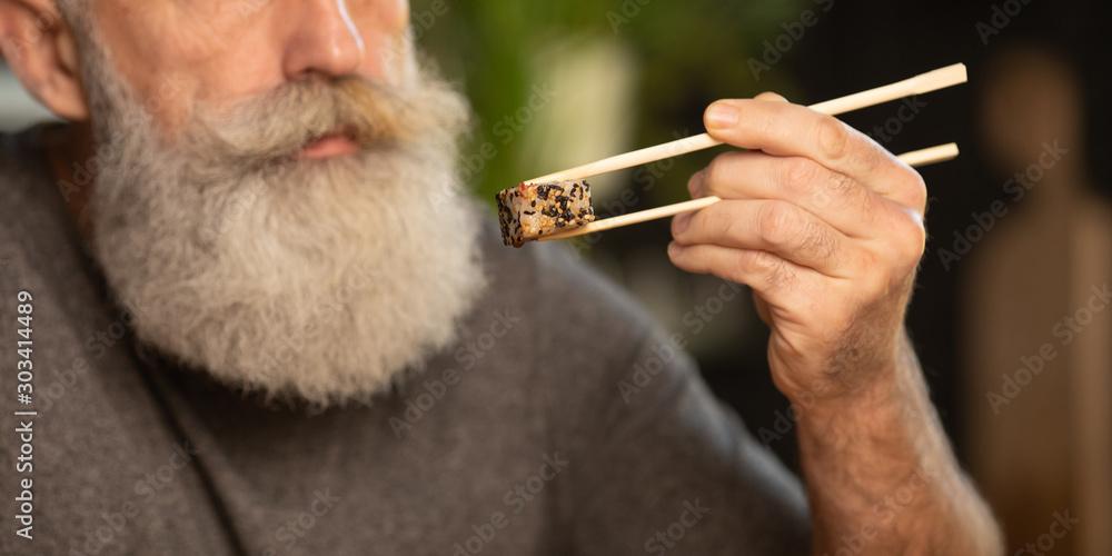 Fototapeta Bearded senior man eating sushi at home.