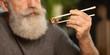 Bearded senior man eating sushi at home.
