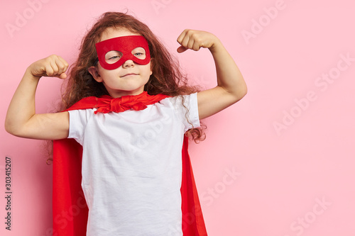 Fototapeta Beautiful little curly girl wearing red hero suit and mask showing how she is strong isolated over pink background obraz