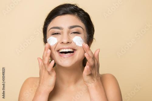 Carta da parati Head shot portrait happy Indian woman applying face cream