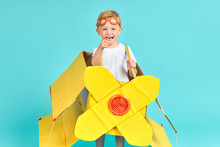 Small Little Smiling Boy With Blond Hair Stand Wearing Toy Yellow Airplane Dream Of Becoming Pilot In Future. Aviation And Sky Concept, Children 's Fantasy