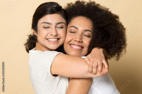 Fotografia Smiling diverse girls with closed eyes, best friends hugging