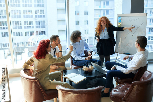 Fotomural  A female boss debating with employees during efficiency charts presentation