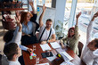 Cheerful team of caucasian young co-workers joined hands together finishing up successful and lucky business meeting in modern conference office, papers, colorful pencils on table. Creative workers