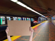 Young Hands Holding A Brown Board With Metro Train In The Background
