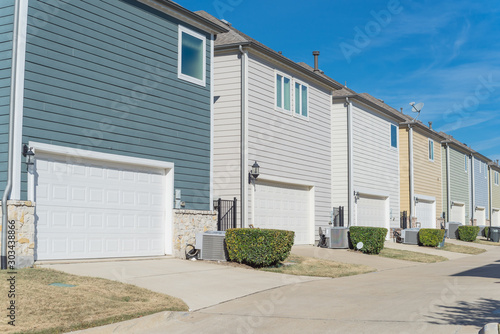 Canvas Prints Narrow alley Concrete back alley of residential neighborhood line of two-car garage door colorful houses near Dallas
