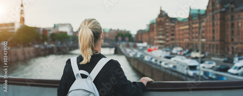 Panoramic rear view of adult woman tourist with backpack enjoying historic wareh Canvas