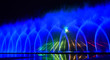 canvas print picture - Colorful water fountains. Beautiful laser and fountain show. Large multi colored decorative dancing water jet led light fountain show at night. Dark background.