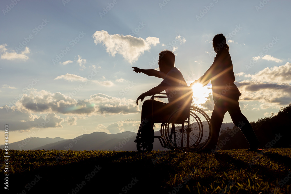 Fototapety, obrazy: Disabled handicapped young man in wheelchair with his wife at sunset.