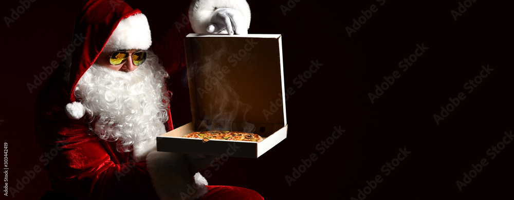 Fototapety, obrazy: Cool Santa Claus in sunglasses holding big hot steaming pizza offering with copy space. Banner. New year Xmas fast food