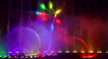 Colorful Water Fountains. Beautiful Laser And Fountain Show. Large Multi Colored Decorative Dancing Water Jet Led Light Fountain Show At Night. Dark Background.