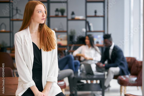 Young caucasian redhaired businesswoman dressed in white blazer stand dreaming looking side