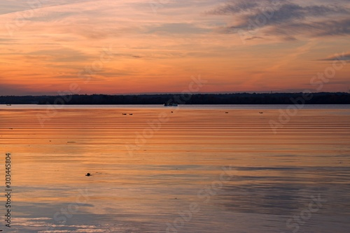 Vivid sunset over the Belmont Bay of water, with coast in silhouette