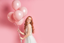 Cute Young Caucasian Woman Holding A Lot Of Pink Air Balloons Isolated Over Pink Background. Smile, Happy