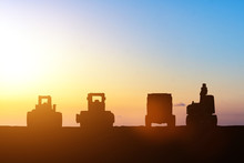 Silhouette Of Excavator And Truck At Construction Site On Sunset. Heavy Machine Equipment For Excavation Works At Civil Industrial Construction