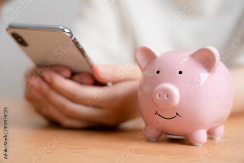 Fototapeta 豚の貯金箱とスマートフォン obraz
