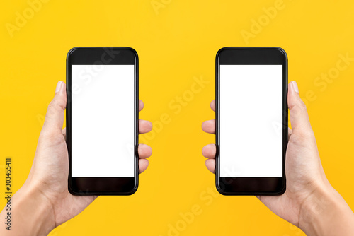 Foto  Two hands holding mobile phones on yellow background with empty screens