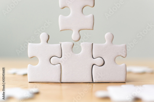 Photo White jigsaw puzzle connecting together