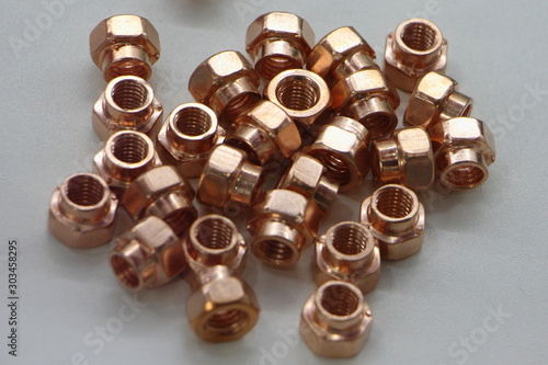 Fotografie, Tablou New copper metal nuts on white background close up