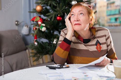Photo  Mature woman calculates utility costs in the new year