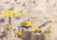 Toy Construction Machinery On The Sand Background