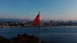 Aerial point of view shot of the Turkish flag flying over Istanbul at dawn.
