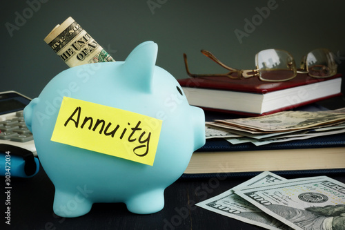 Photo Annuity written on yellow sheet and piggy bank with money.