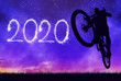 canvas print picture - Forward to the New Year 2020. Cyclist jumping on the bicycle with night sky at the background.