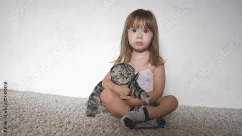 Pinturas sobre lienzo  Happy little girl hugs and kisses a Scottish fold cat