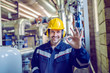 Leinwandbild Motiv Smiling satisfied blue collar worker in working clothes, with helmet and hardhat standing in factory and showing okay sign.
