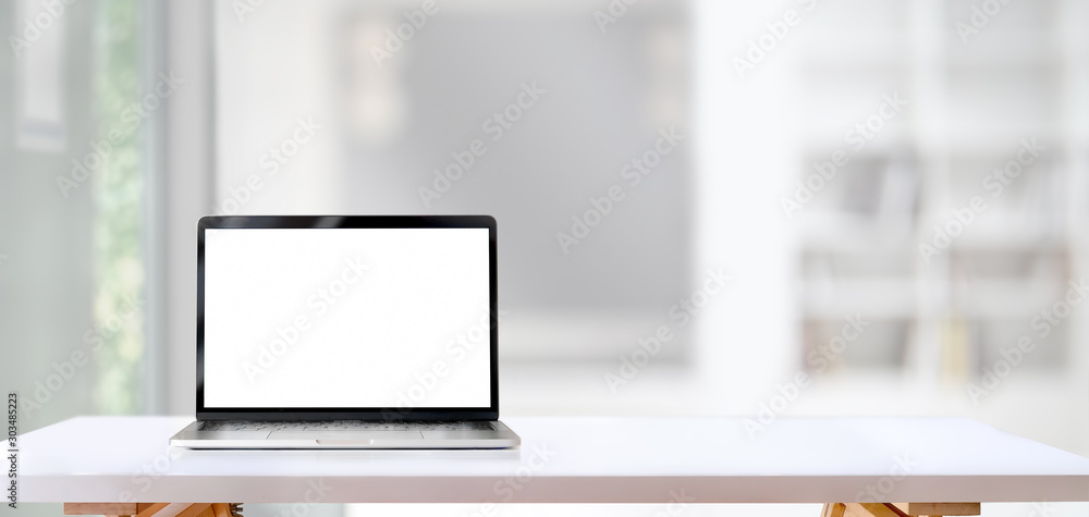 Fototapety, obrazy: Blank screen laptop computer on white wooden table with living room in the background