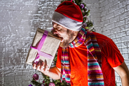An angry and aggressive Santa stands near the Christmas tree and holds a New Year's gift Wallpaper Mural