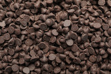 Delicious chocolate chips as background, top view