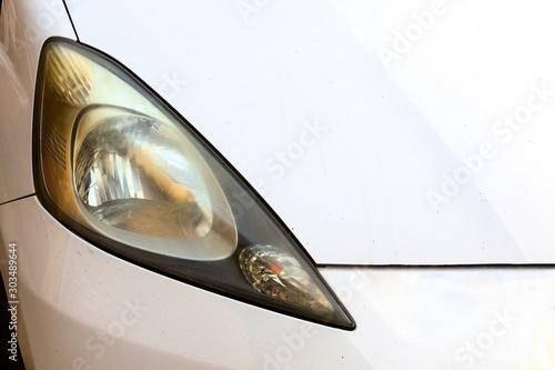 Obraz Close up hazy yellowed dirty car headlight. Unpolished cloudy foggy front headlight of old car. Car headligh cleaning concept. - fototapety do salonu