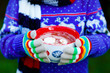 canvas print picture - Closeup of hands of child holding big cup with snowflakes and hot cocoa and chocolate drink and marshmallows. Kid in winter sweater, long warm scarf and colorful gloves. On cold winter day