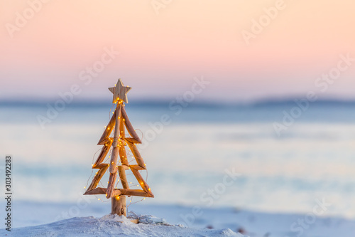 Obraz Christmas tree with fairy lights on the beach in summer - fototapety do salonu