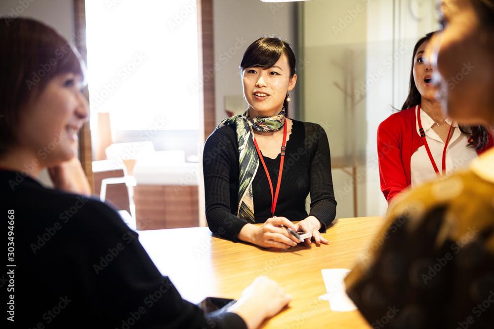 Fototapeta 会議の内容を聞く女性