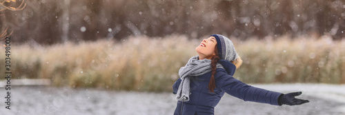 Winter snowing happy Asian girl with open arms enjoying snow fall falling snowflakes wearing cold weather scarf, hat, gloves warm jacket banner panorama. Girl walking outdoor nature woods background.