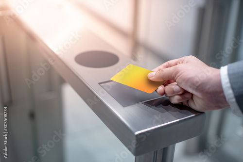 Obraz Businessman hand with business wear using yellow smart card to open automatic gate machine in office building. Working routine concept - fototapety do salonu