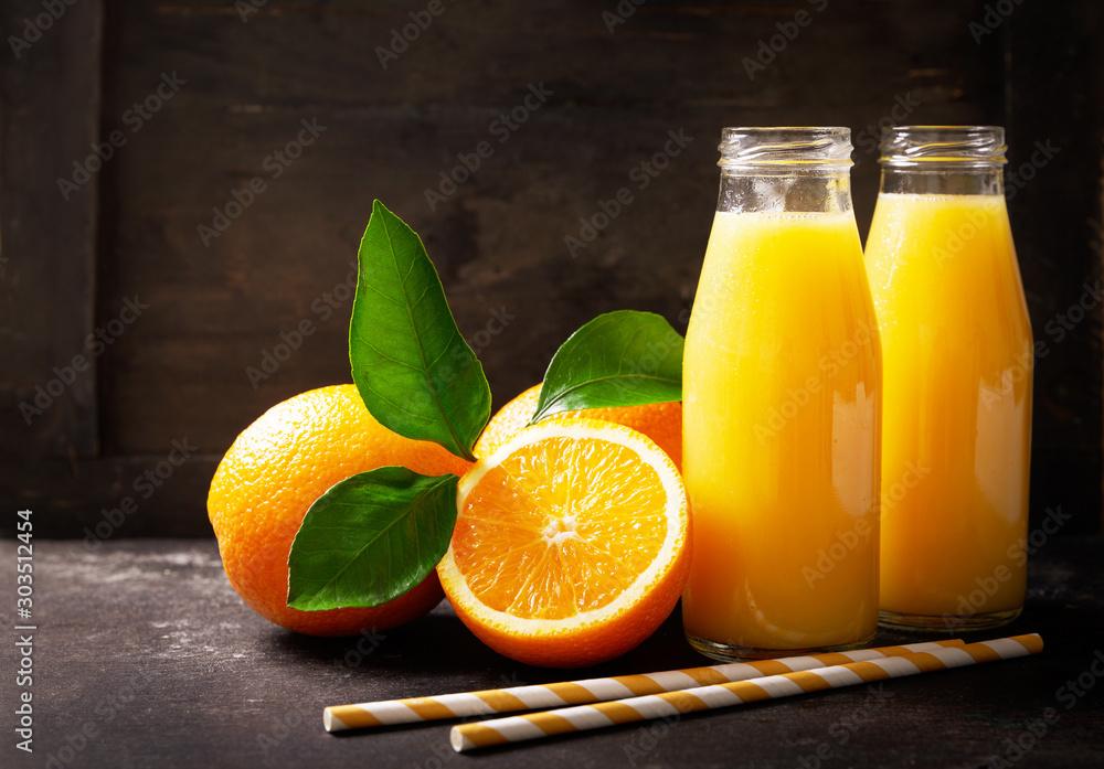 Fototapeta bottles of fresh orange juice with fresh fruits