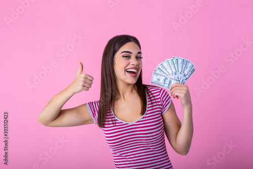 Fotografie, Obraz  Portrait of a cheerful young woman holding money banknotes and showing thumb up