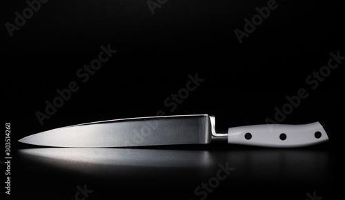 Fotografija Kitchen knife with a white handle on a black background